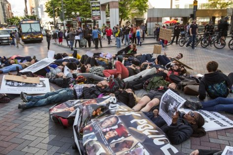 A small group of demonstrators protesting police brutality lay down in the intersection of Pine Street and 4th Avenue downtown Wednesday, April 29, 2015.