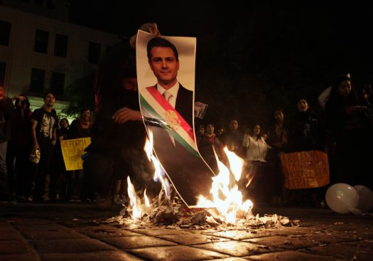 A demonstrator burns a photograph of Mexico's President Enrique Pena Nieto during a protest in support of the 43 missing Ayotzinapa students, in Monterrey November 20, 2014. Thousands took to the streets across Mexico protesting over President Enrique Pena Nieto's handling of the apparent massacre of the trainee school teachers after their abduction on the night of September 26. Mexico has been convulsed by protests since the 43 students were taken from the southwestern city of Iguala by police working with a local drug gang and then very likely incinerated, according to the government, which is still investigating the incident. REUTERS/Daniel Becerril (MEXICO - Tags: CIVIL UNREST CRIME LAW POLITICS)